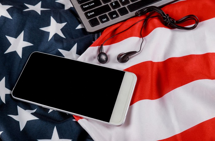 A smartphone and a laptop on an American flag.