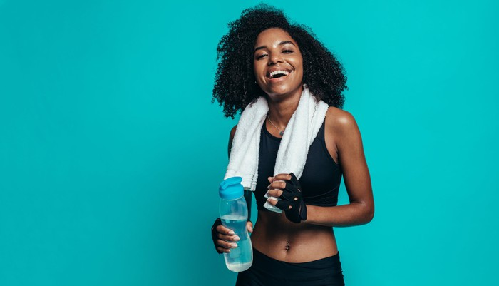 A smiling woman in workout gear with a towel around her neck and holding a water bottle.