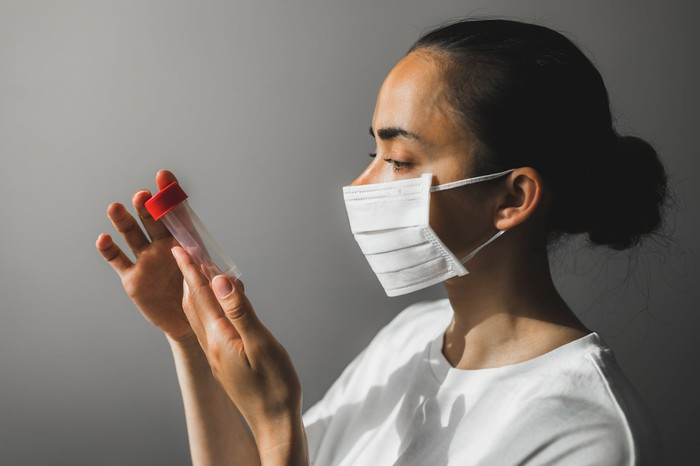 A woman in a medical mask looking at a test tube.