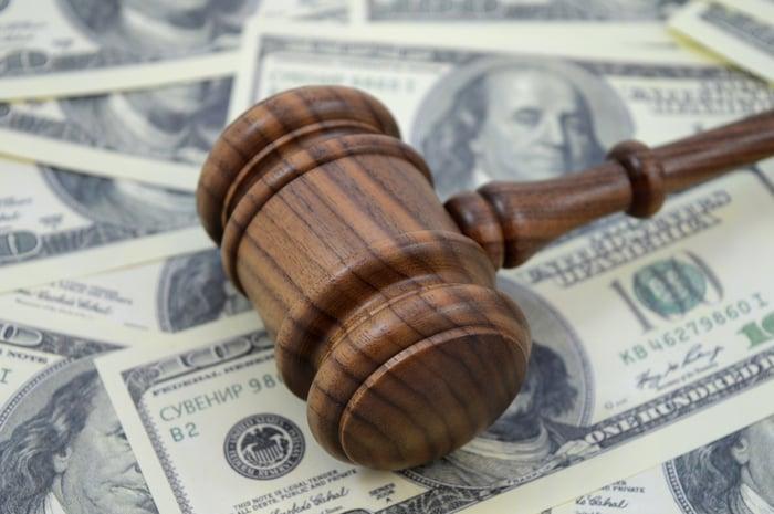 judge's gavel on 100 dollar bills representing lawsuit