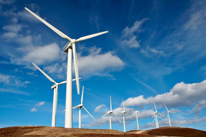A wind power farm against a cloudy blue sky.