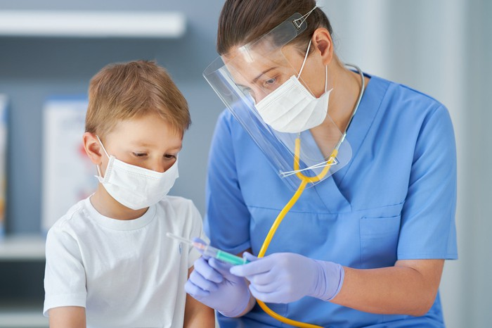 Healthcare working showing a syringe to a child