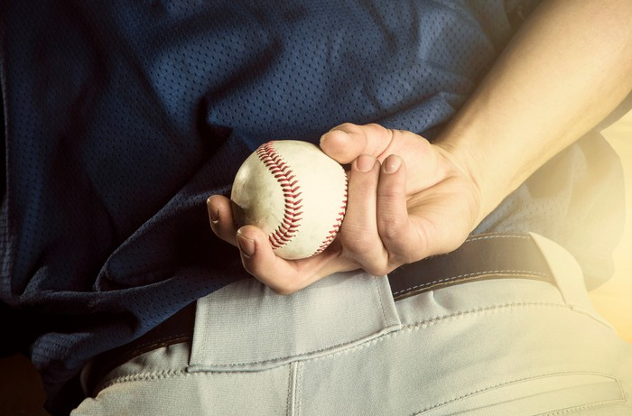 A baseball in the hand of a pitcher, hidden behind the player's back.