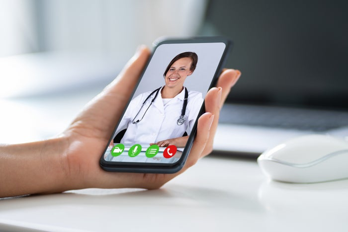 A person's hand holding a phone in a video chat with a doctor on a smartphone.