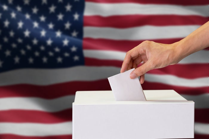 Person drops folded ballot into box, American flag drapes across the background