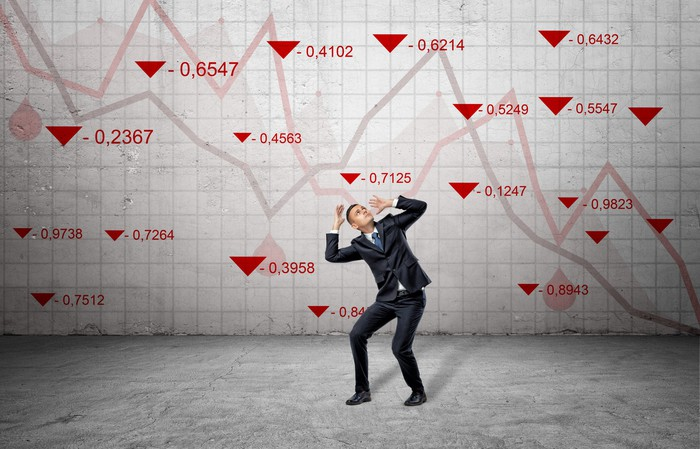 A scared businessman cowers near a concrete wall with red stock market indexes and falling statistic lines