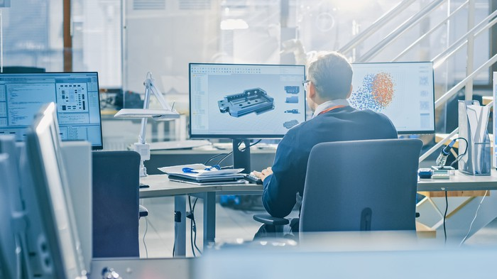 A man works behind a computer screen.