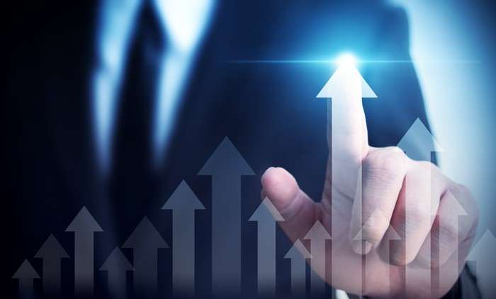 A businessman touches an arrow which rises higher than other arrows.