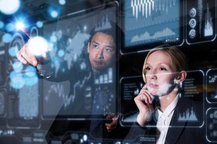Two IT workers look at screens showing graphs and planning tools.