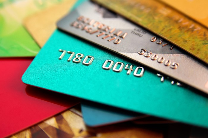 Blue, silver, and gold credit cards stacked on top of one another.