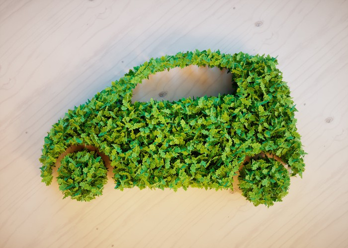 A car silhouette made out of green leaves.