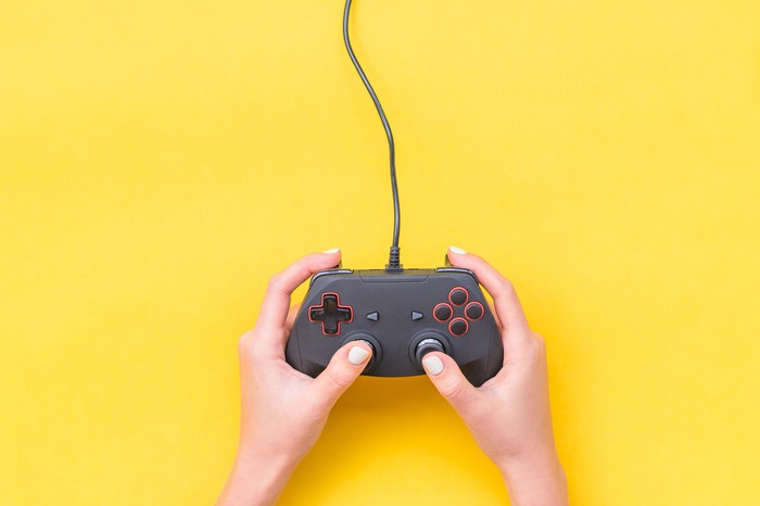A pair of hands holding a video game controller on a yellow background