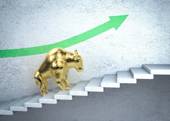 A golden bull on a staircase underneath an arrow pointing up and to the right.
