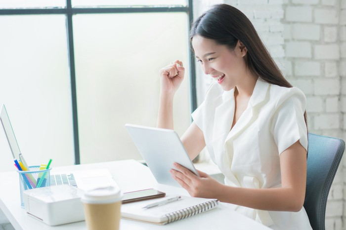 A woman smiles as she looks at her share holdings on her laptop.