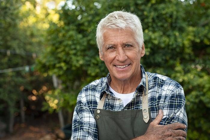 Smiling older gardener wearing an apron outdoors.