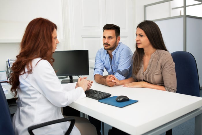 a couple consulting a doctor in an office