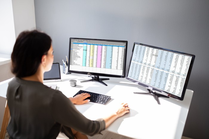 A woman works on a database across two monitors.
