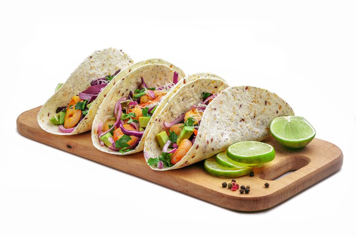 Three tacos sitting on a wooden board with lime beside them.