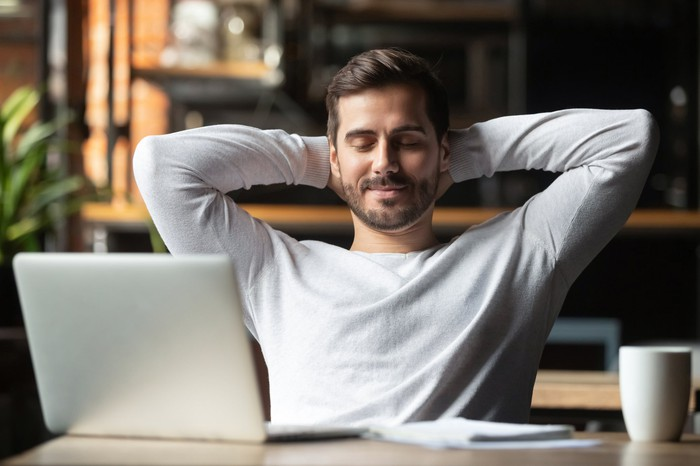Relaxed happy man at desk meditating in front of laptop