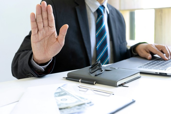 A man in a business suit holds up the palm of his hand facing the viewer to indicate hesitation.