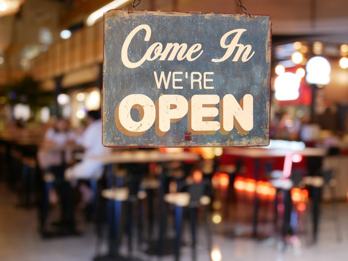 Photo of a sign reading Come in we're open, on the glass door of a busy restaurant.