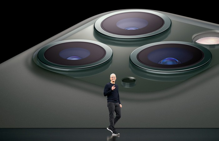 Tim Cook on stage with a image of three cameras on the back of an iPhone projected on the screen behind him.