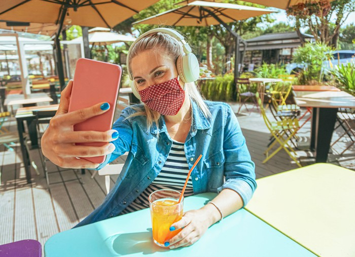 A young woman takes a selfie with her phone at an outdoor cafe.