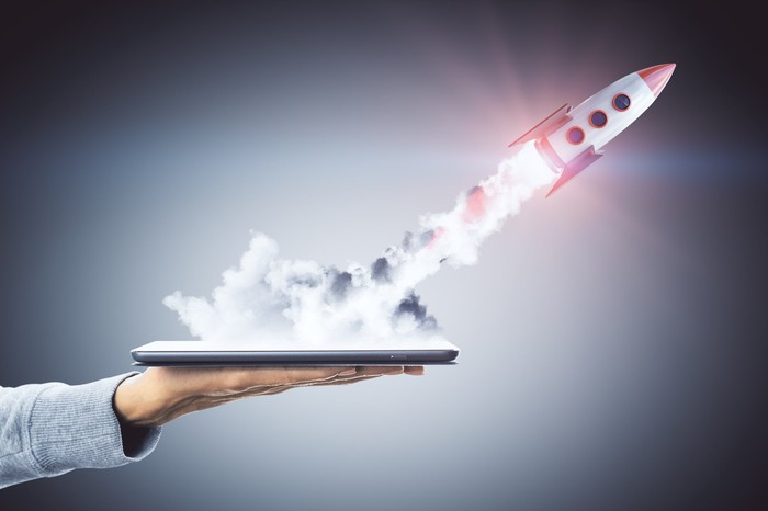 A rocket takes off from a portable screen.