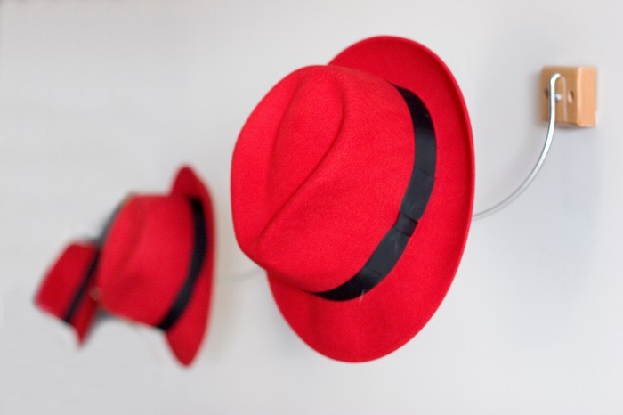 Three red fedoras hanging on wall hooks in a white hallway.