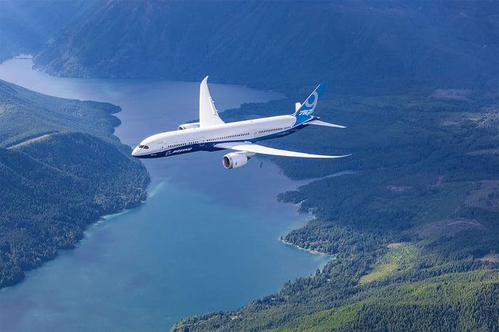 A Boeing 787 Dreamliner flying over a river.