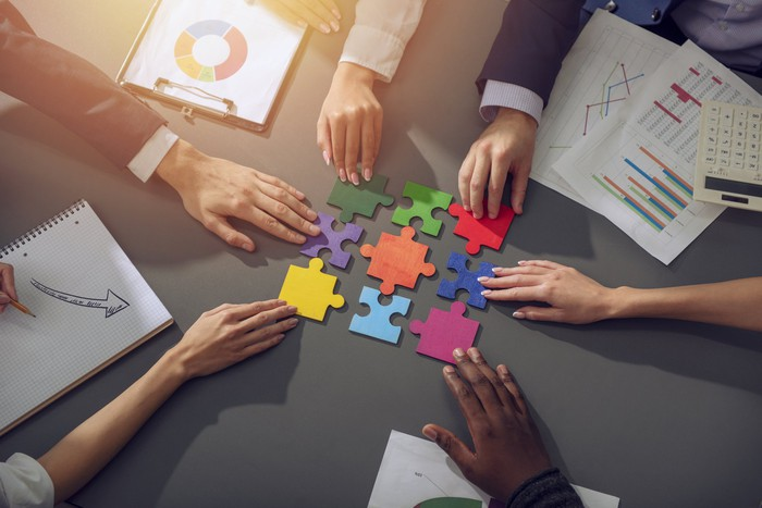 Multi-colored puzzle pieces being assembled by business people at a conference table