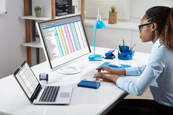 A businesswoman works on computer spreadsheets in a home office.