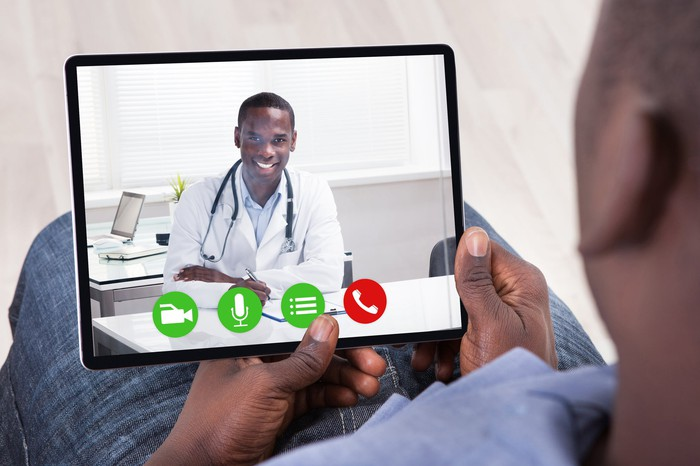 Doctor and patient conferring via tablet computer.