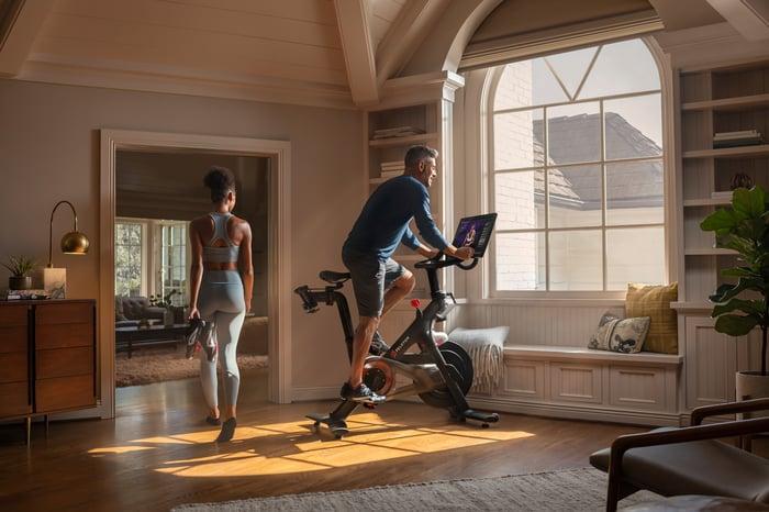 A man rides a Peloton bike as a woman walks behind him.