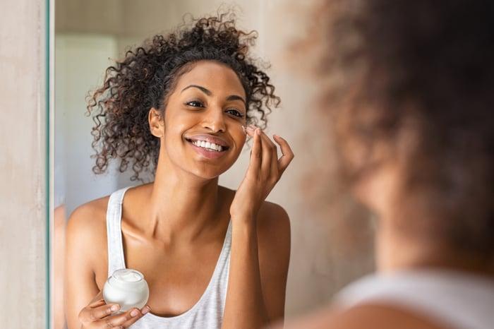 Woman applying face cream.