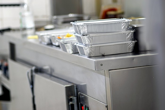 Multiple trays of food in takeout containers on a steel kitchen counter
