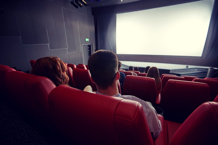 A few people sit in a movie theater.