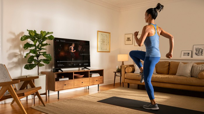 A younger woman follows a Peloton online class to work out in her living room.