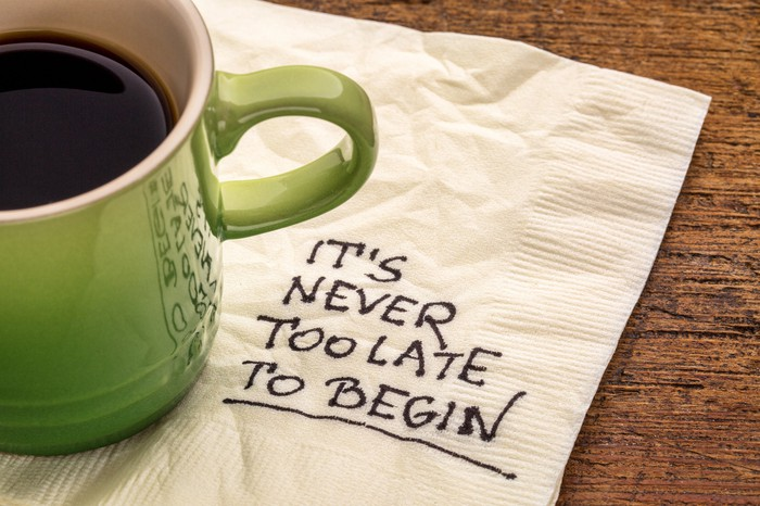 Coffee cup sitting on napkin that reads It's never too late to begin