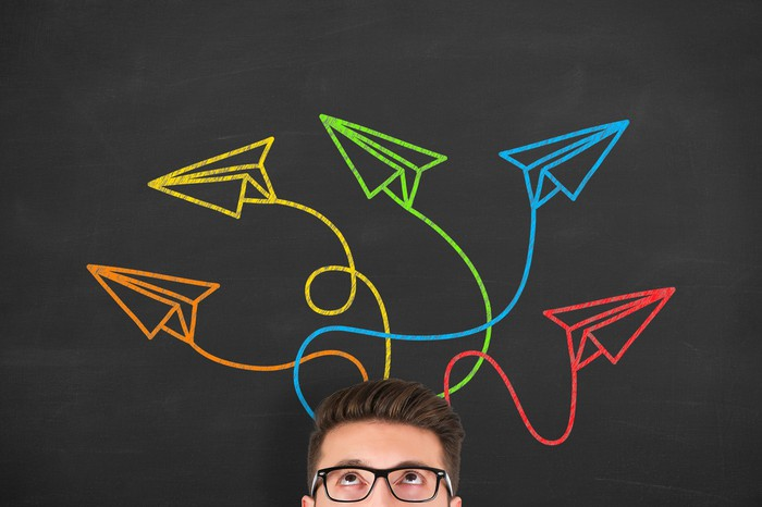 A man looks up at several drawings of colorful paper planes flying around his head.