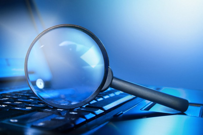 A magnifying glass on a laptop keyboard.