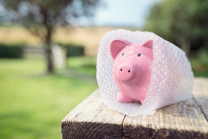 A piggy bank is shielded by bubble wrap, representing the concept of savings protection.