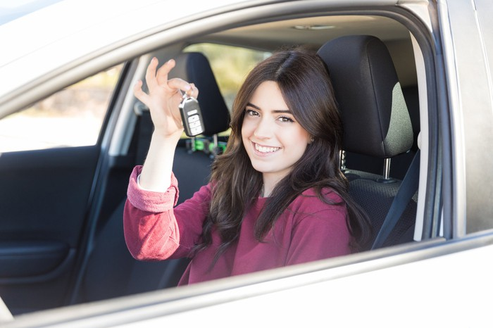 A young woman smiles in a car she just bought while holding up the keys.