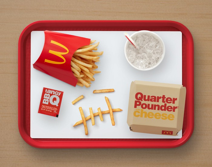 A McDonald's tray with a Quarter Pounder, Large Fries, a Sprite, and a pack of BBQ sauce/
