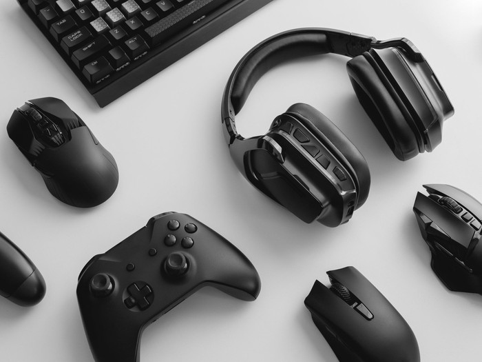Assorted PC gaming equipment, including mice, a controller, headphones, and a keyboard.