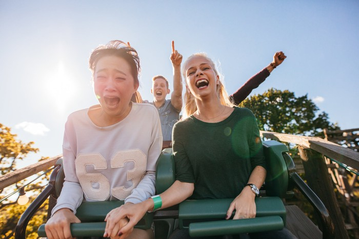 Several people screaming and smiling on a plummeting rollercoaster ride.