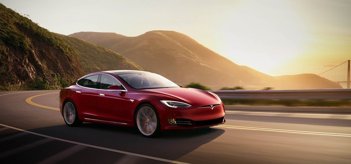 A Tesla Model S driving on a curvy mountain road with the sunset in the distance.