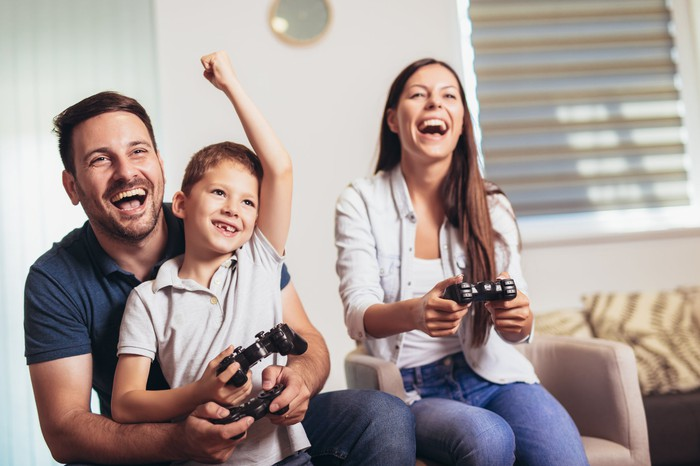 A husband wife and son play video games together.