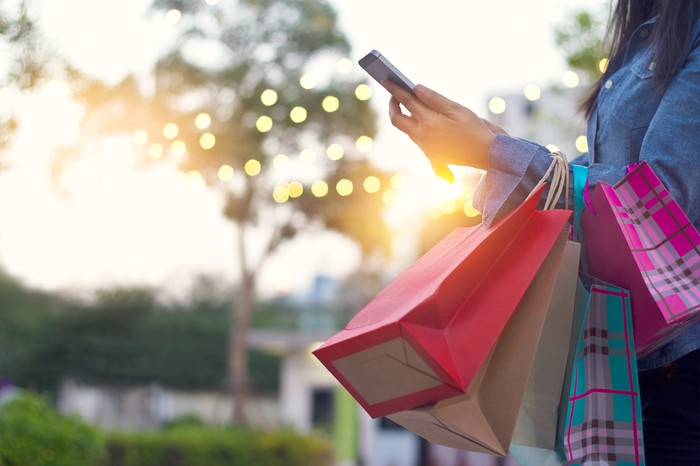 A woman checks her phone while carrying shopping bags.