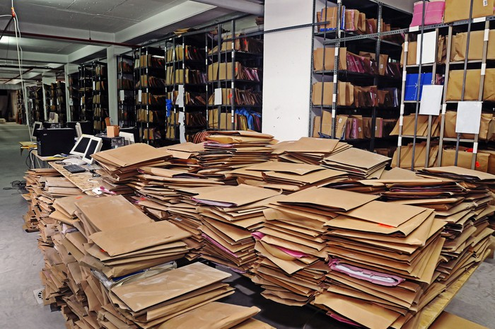 A mess of paper files on the ground, with rows of file storage racks in the background